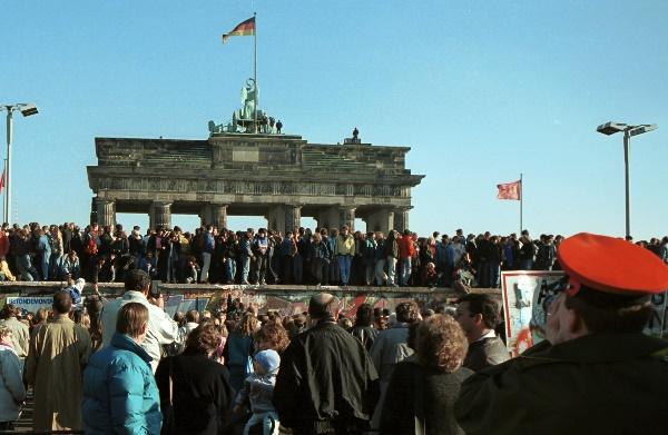 Menschen auf der Berliner Mauer vor dem Brandenburger Tor.