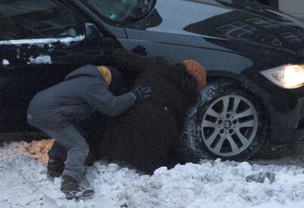 Mit der Hand wird der Schnee in der Fahrspur beiseite gedrückt.