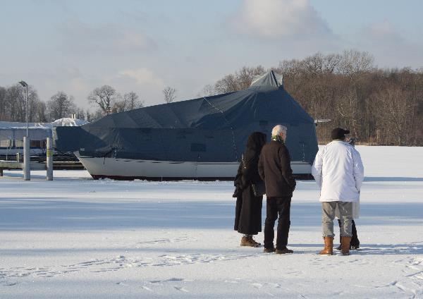 Menschen auf dem Eis vor einem Boot im Eis