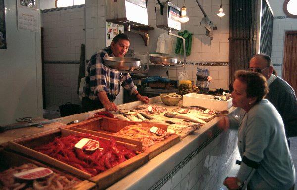 1997, Spanien, Andalusien, Costa del Sol, Markt in Almunecar. Verkäufer und Kunden am Fischstand.